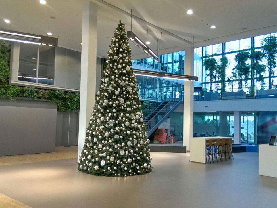 Kunst kerstboom groot versierd in hal